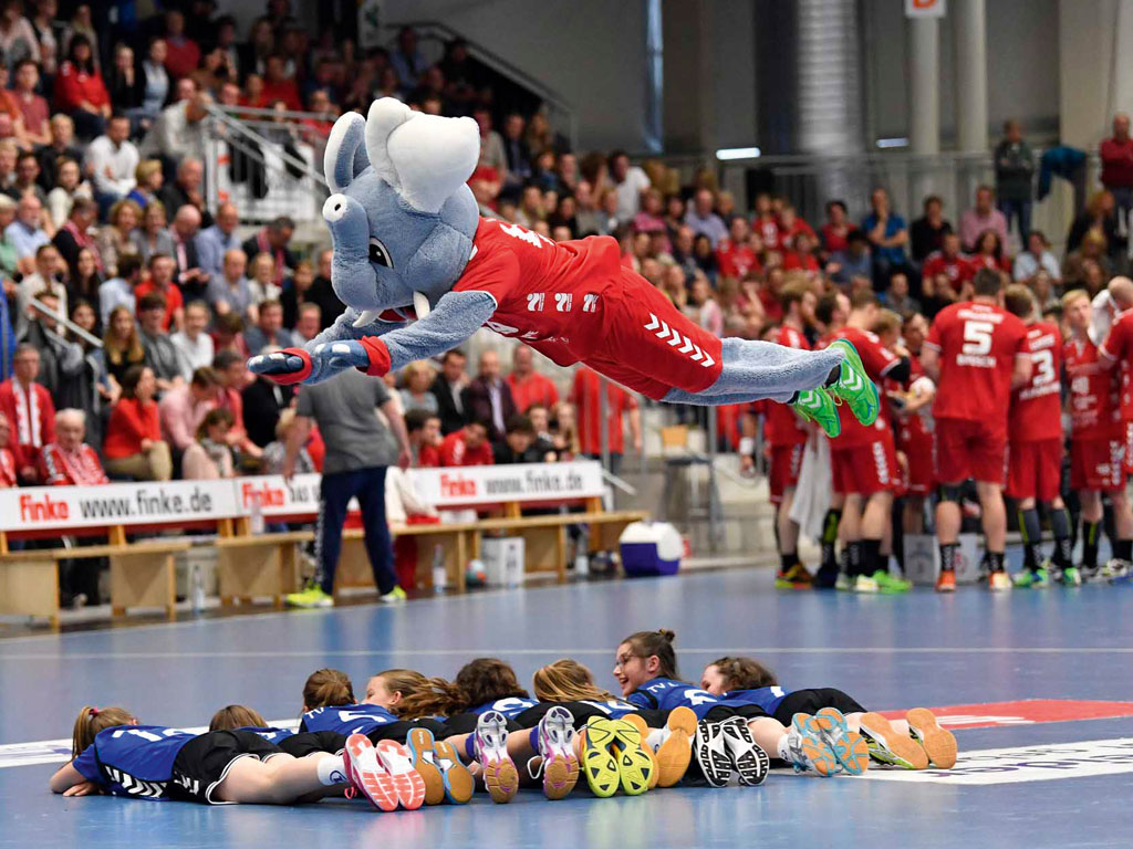 Westpress Arena Hamm - Maskottchen springt über liegende Kinder beim Handballspiel des ASV Hamm.